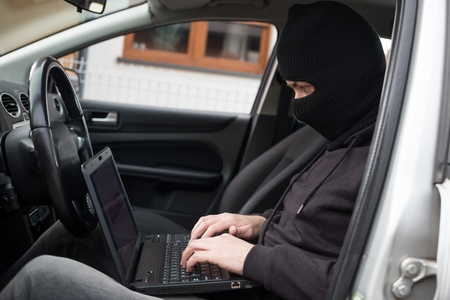 disarm: Car Thief tries to disarm car security systems and immobiliser with laptop computer. Car thief, car theft