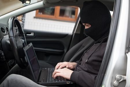 robo de autos: Ladrón de coches intenta desarmar a los sistemas de seguridad del coche y inmovilizador con el ordenador portátil. ladrón de coches, el robo de automóviles