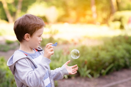 bulles de savon: Childrens Day.  Little boy blowing soap bubbles in the park Banque d'images