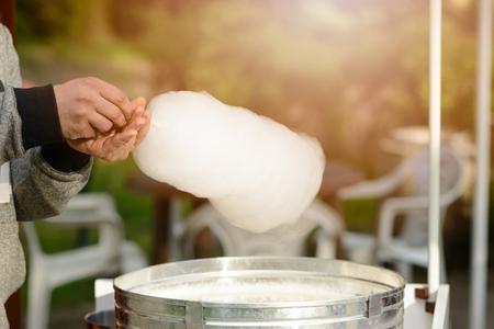 Los hombres se preparan algodón de azúcar en el parque. Día de los niños Foto de archivo