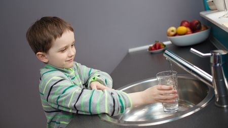 Child - 7 year old boy pouring tap water into a glass