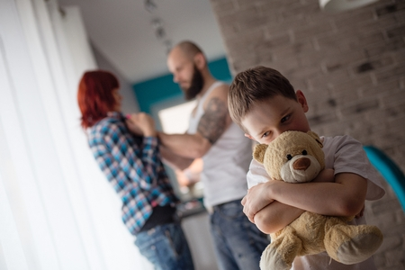 Sad, desperate little boy during parents quarrel - hugging his friend old teddy bear 스톡 콘텐츠