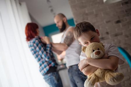 Sad, desperate little boy during parents quarrel - hugging his friend old teddy bear Archivio Fotografico