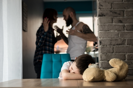 dysfunctional: Sad, desperate little boy during parents quarrel - with his friend old teddy bear