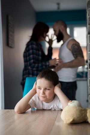 dysfunctional: Sad, desperate little boy during parents quarrel. Clog the ears.