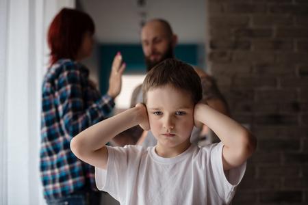 personas discutiendo: Triste, desesperada niño durante los padres disputa. Tapar los oídos.