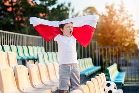 bandera de polonia: Little boy - Polish football team fan - supporter with Polish flag on the stadium Foto de archivo