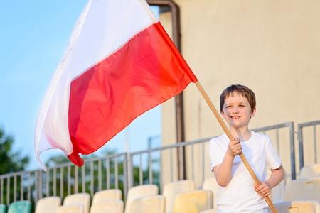 bandera de polonia: Del niño pequeño - ventilador equipo de fútbol polaco - partidario de la bandera polaca en el estadio Foto de archivo