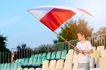 patriotism: Little boy - Polish football team fan - supporter with Polish flag on the stadium Stock Photo