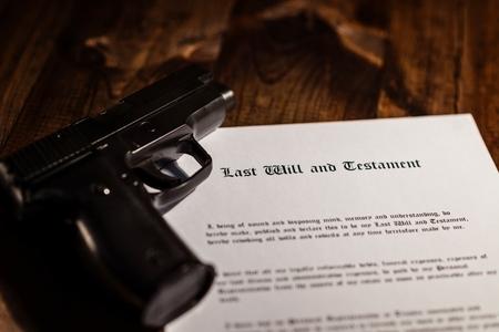 testament: Pistol and testament on desk. Suicide concept Stock Photo