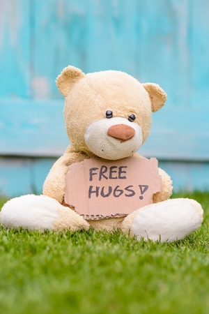 free me: Little old teddy bear sitting on the grass in the garden and holding a piece of cardboard with the information - ree Hugs Stock Photo