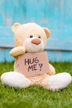 free me: Little old teddy bear sitting on the grass in the garden and holding a piece of cardboard with the information - hug me