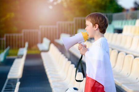 bandera de polonia: Polish football fan - little boy with megaphone and Polish flag supporting national team