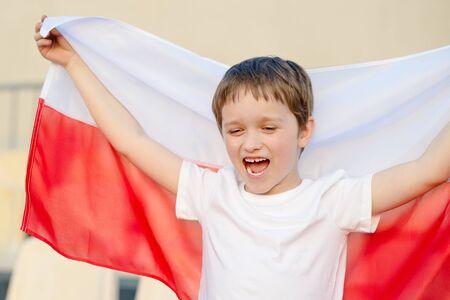 bandera de polonia: aficionado al fútbol polaco - niño pequeño con la bandera polaca apoyo del equipo nacional Foto de archivo