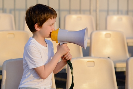 demonstrator: Little football fan with megaphone on the stadium