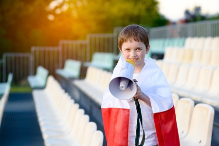 polish flag: Polish football fan - little boy with megaphone and Polish flag supporting national team