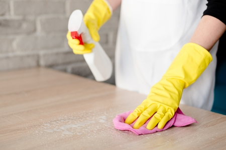 rubber gloves: Woman in yellow rubber gloves cleaning table with pink cloth