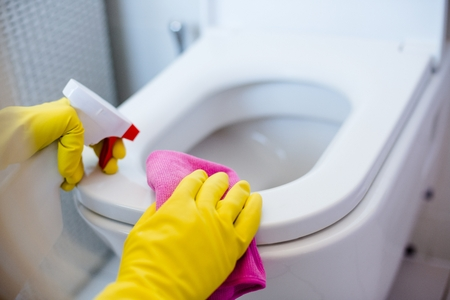 Woman in yellow rubber gloves cleaning toilet with pink cloth Archivio Fotografico