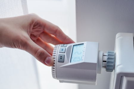 Woman adjusting temperature of home heater in room