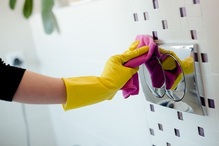 public servants: Woman in yellow rubber gloves cleaning flush button with pink cloth Stock Photo