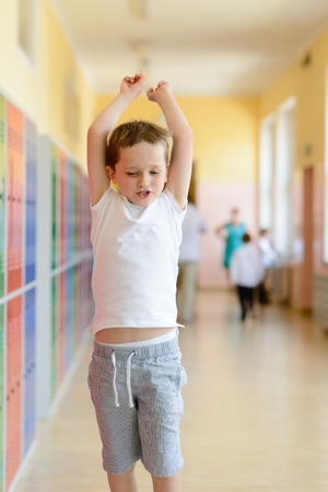 pre teen boy: Happy 7 years old schoolboy running out of school. End of school.