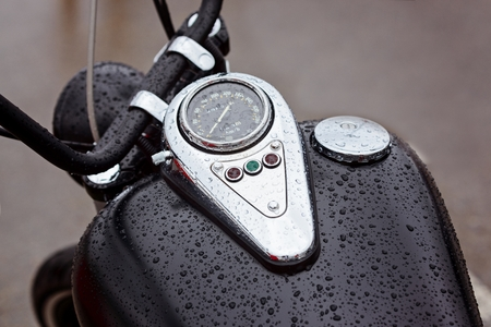 warning lights: Tank with speedometer with warning lights on a motorbike in the rain