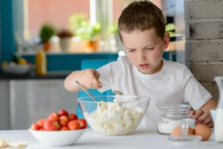 7 year old: 7 year old boy adding sugar to cottage cheese in a bowl. Prepares mini cheesecakes with strawberries