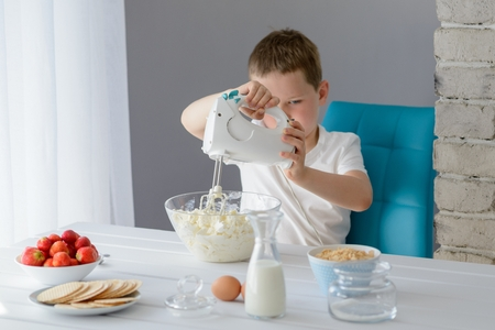electric mixer: 7 year old boy mixing with electric mixer white cottage cheese in a bowl. Prepares mini cheesecakes with strawberries