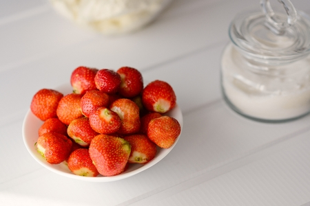 Bowl full of red fresh strawberries. Next to bowl cup with sugar. White wooden table.