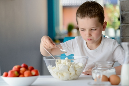 adding sugar: 7 year old boy adding sugar to cottage cheese in a bowl. Prepares mini cheesecakes with strawberries