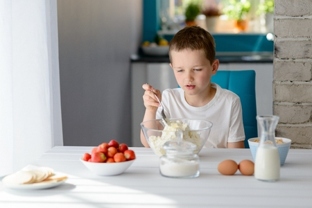 7 year old: 7 year old boy mixing white cottage cheese in a bowl. Prepares mini cheesecakes with strawberries