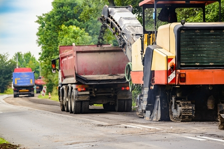 Road works. Asphalt removing machine loading powdered asphalt on the truck Stock Photo