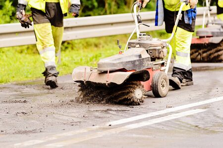 Worker removes with machine the upper layer of the tarmac