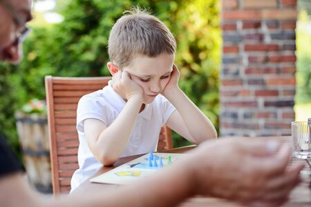 ludo: Little boy playing ludo board game on the terrace Stock Photo