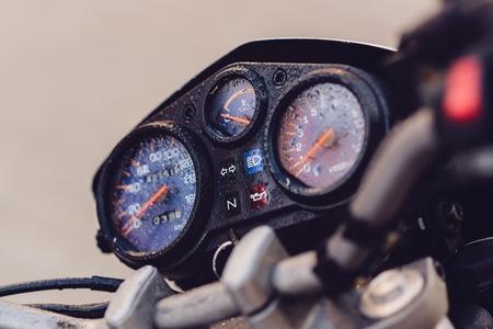 raining: panel de control de la moto clásica con velocímetro y revoluciones del contador en la lluvia Foto de archivo