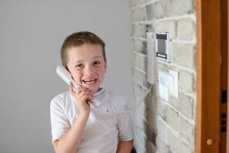 interphone: Little baby boy talking on intercom mounted on wall