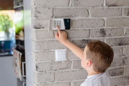 Kleine baby jongen duwt een knoppen op het alarm toetsenbord - binnenlandse veiligheid systeem opgezet op muur