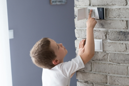 Little baby boy pushes a buttons on the alarm keypad - home security system mounted on wall Banco de Imagens - 59795424