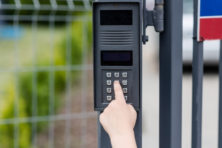 Little child boy pushes a button on the intercom mounted on the gate