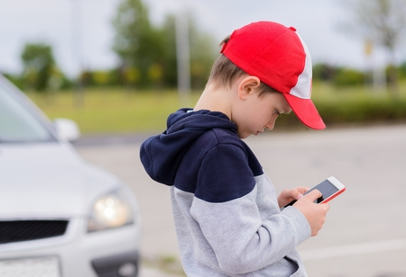 pay attention: Child busy playing the smartphone mobile games does not pay attention to the moving car. Boy child playing mobile games on smartphone on the street Stock Photo