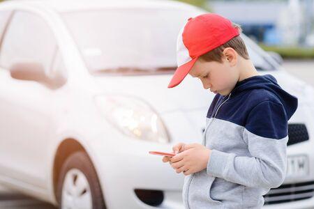 poner atencion: Ni�o ocupados jugando a los juegos m�viles de tel�fonos inteligentes no presta atenci�n al autom�vil en movimiento. El ni�o jugando juegos de m�vil en el tel�fono inteligente en la calle