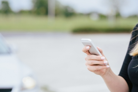 poner atencion: Mujer con el tel�fono jugar a los juegos m�viles de tel�fonos inteligentes no presta atenci�n al autom�vil en movimiento. Mujer que juega a juegos m�viles en el tel�fono inteligente en la calle
