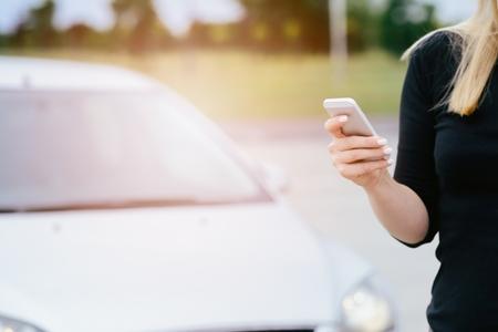 poner atencion: Mujer con el teléfono jugar a los juegos móviles de teléfonos inteligentes no presta atención al automóvil en movimiento. Mujer que juega a juegos móviles en el teléfono inteligente en la calle