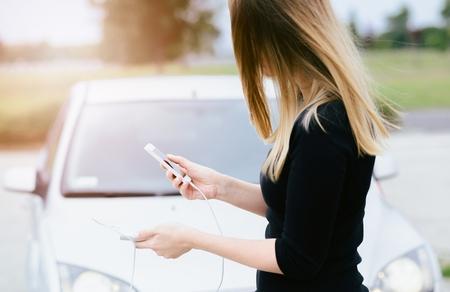 Mujer con el teléfono y el banco de potencia de jugar a los juegos móviles de teléfonos inteligentes no presta atención al automóvil en movimiento. Mujer que juega a juegos móviles en el teléfono inteligente en la calle