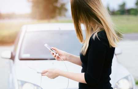 pay attention: Woman with phone and power bank playing the smartphone mobile games does not pay attention to the moving car. Woman playing mobile games on smartphone on the street