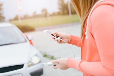 prestar atencion: Mujer con el teléfono y el banco de potencia de jugar a los juegos móviles de teléfonos inteligentes no presta atención al automóvil en movimiento. Mujer que juega a juegos móviles en el teléfono inteligente en la calle