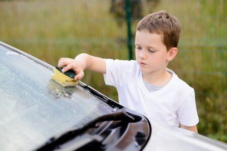 Little boy washing silver car in the garden. Summer Stock Photo