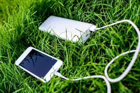 Powerbank charging white smartphone on grass