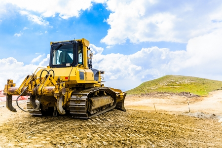 unsurfaced road: Yellow bulldozer on tracks at the mountain road construction Stock Photo
