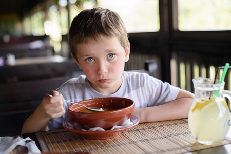 gastronome: Little child boy enjoying his delicious soup in restaurant
